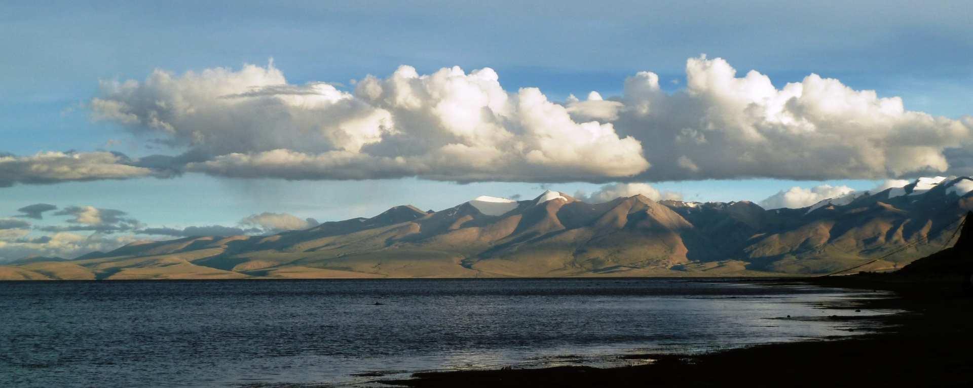 Holy lake Manasarovar view with fairytale clouds.